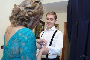 madre ayuda al novio a vestirse.